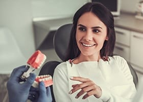 Patient in dental chair looking at smile model