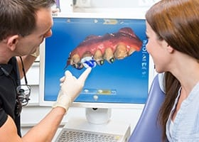 Dentist and patient looking at 3D oral images