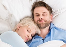 Man and woman sleeping soundly in bed