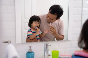 happy father and daughter brushing together