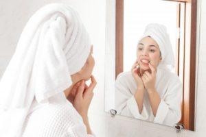 woman looking at teeth in the mirror
